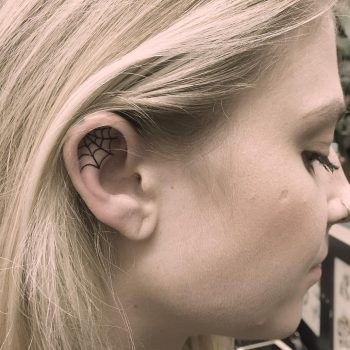 Spider web tattoo on the right ear
