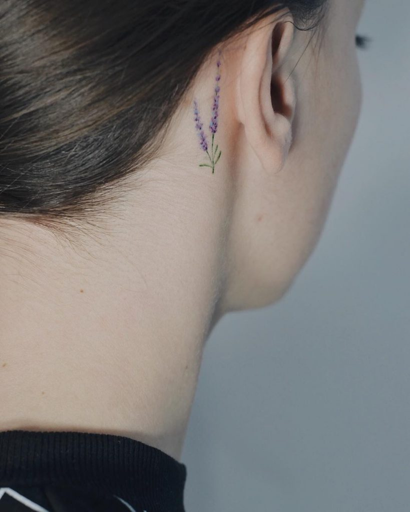 Tiny lavender tattoo behind the right ear