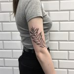 Tropical branch tattoo on the arm