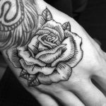 Woodcut style rose tattoo on the hand