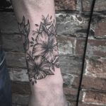 Wrapping blackwork hibiscus tattoo