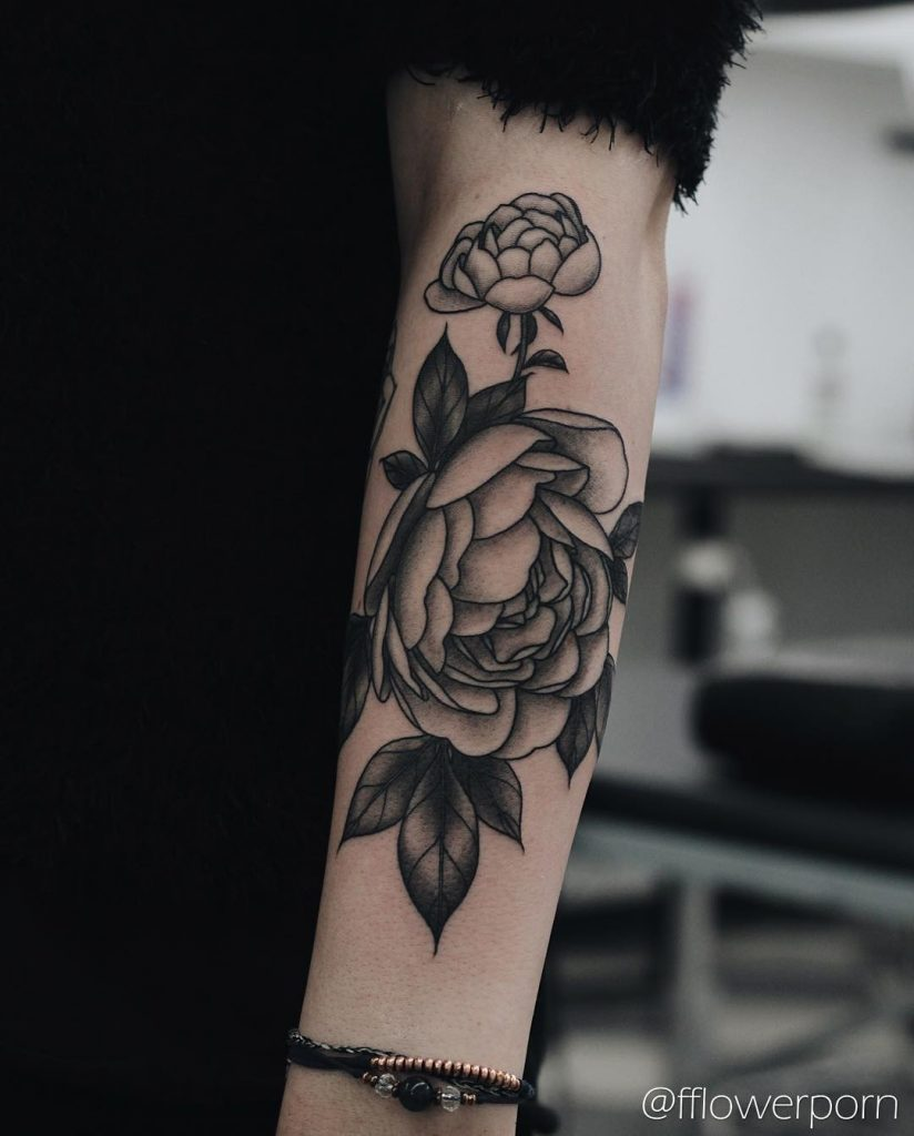 Black and grey peony tattoo on the left forearm