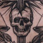 Cross pierced skull tattoo