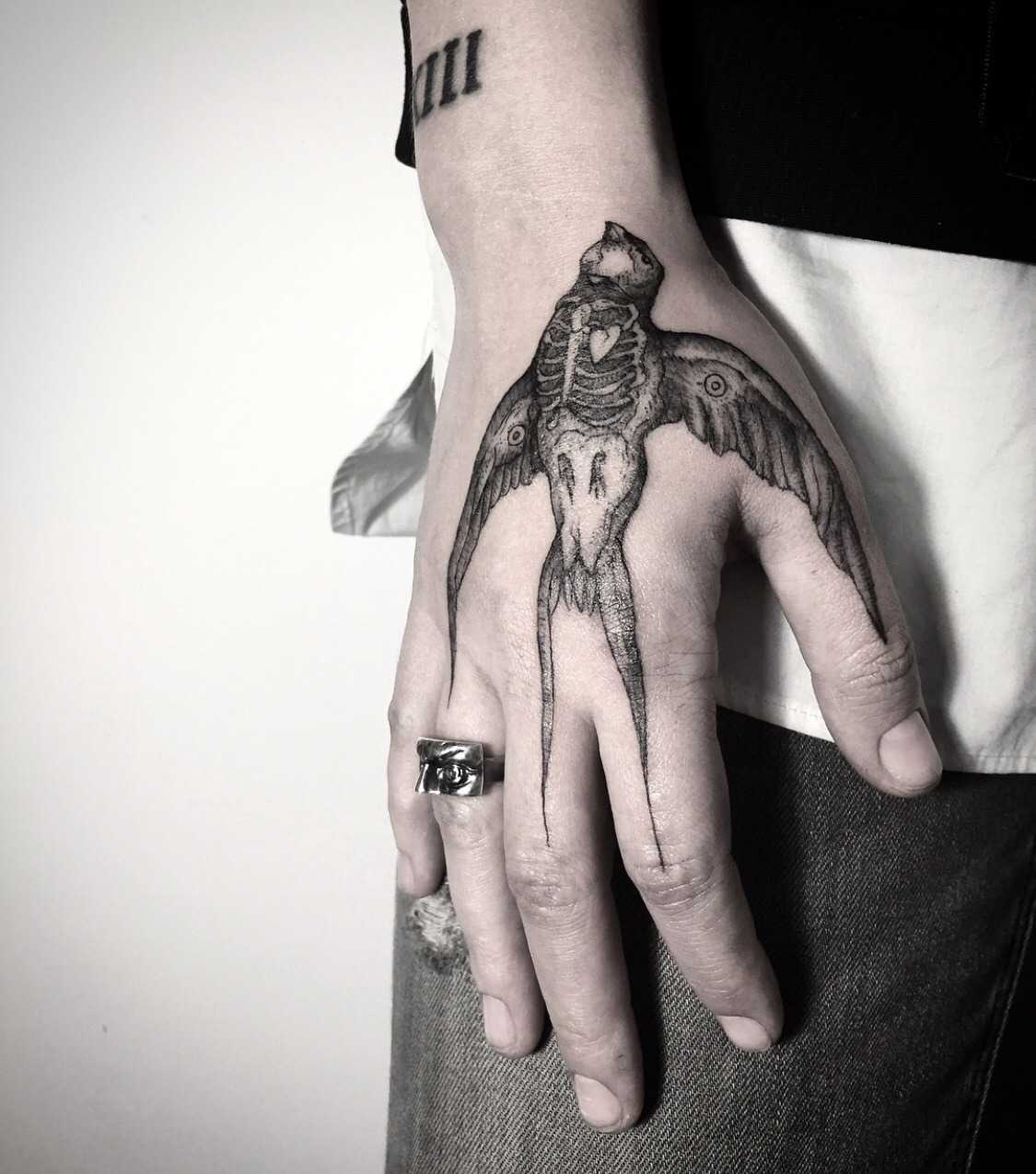 Dead bird tattoo on the hand