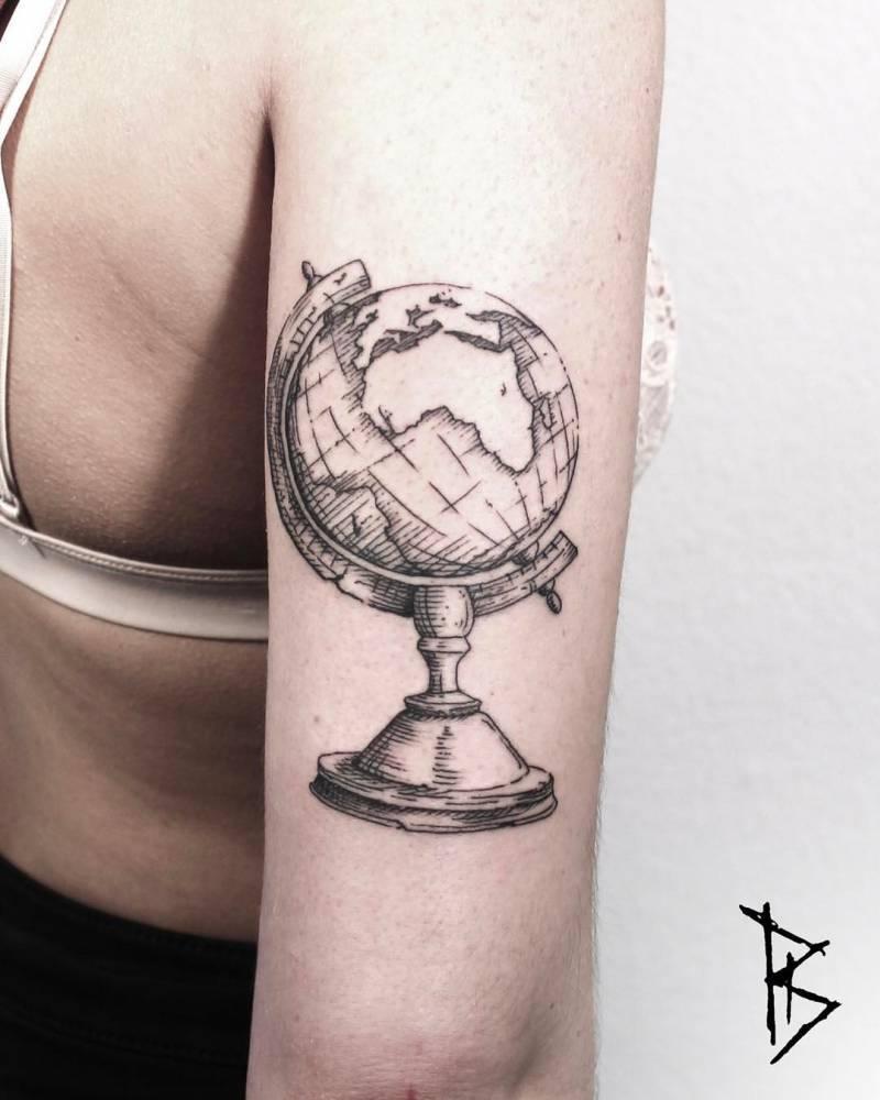 Globe tattoo on the triceps by Loïc Lebeuf