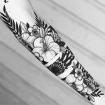 Negative space floral arm tattoo