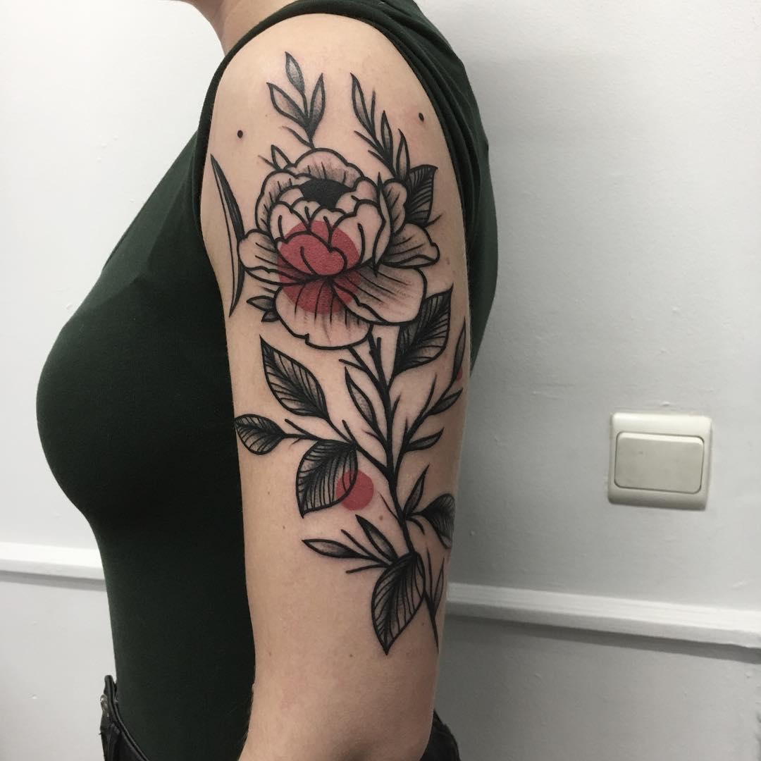 Red and black flower tattoo on the arm