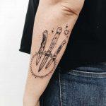 Three knives and sun tattoo