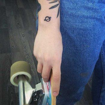 Tiny Saturn tattoo on the wrist