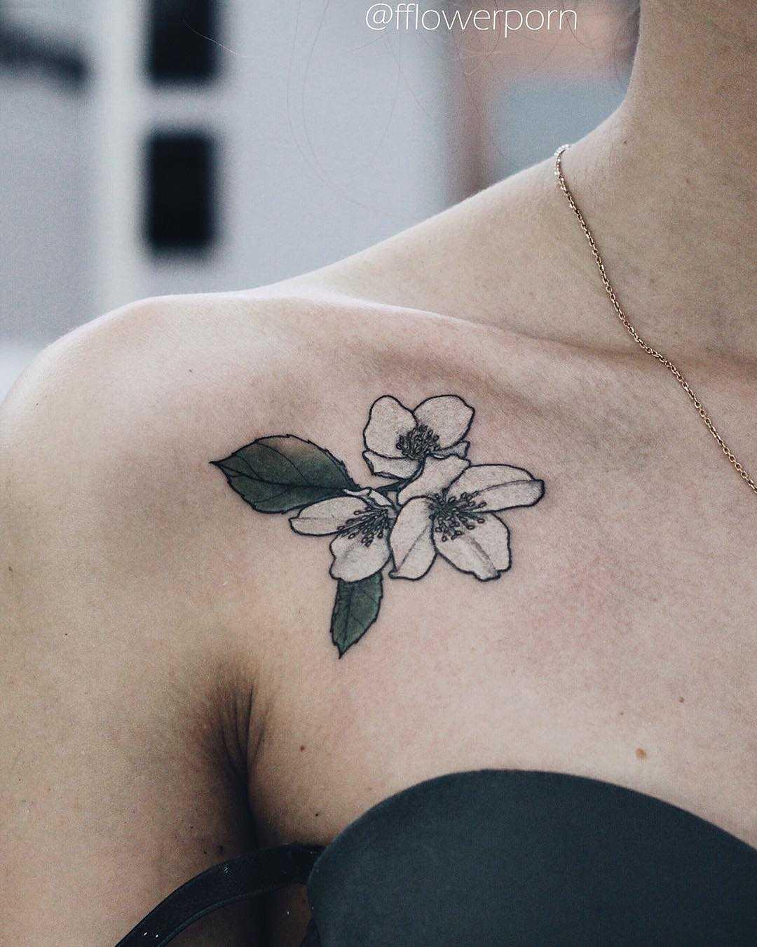 Tiny jasmine tattoo on the collarbone