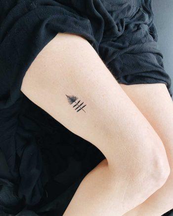 Tiny talisman tattoo on the thigh