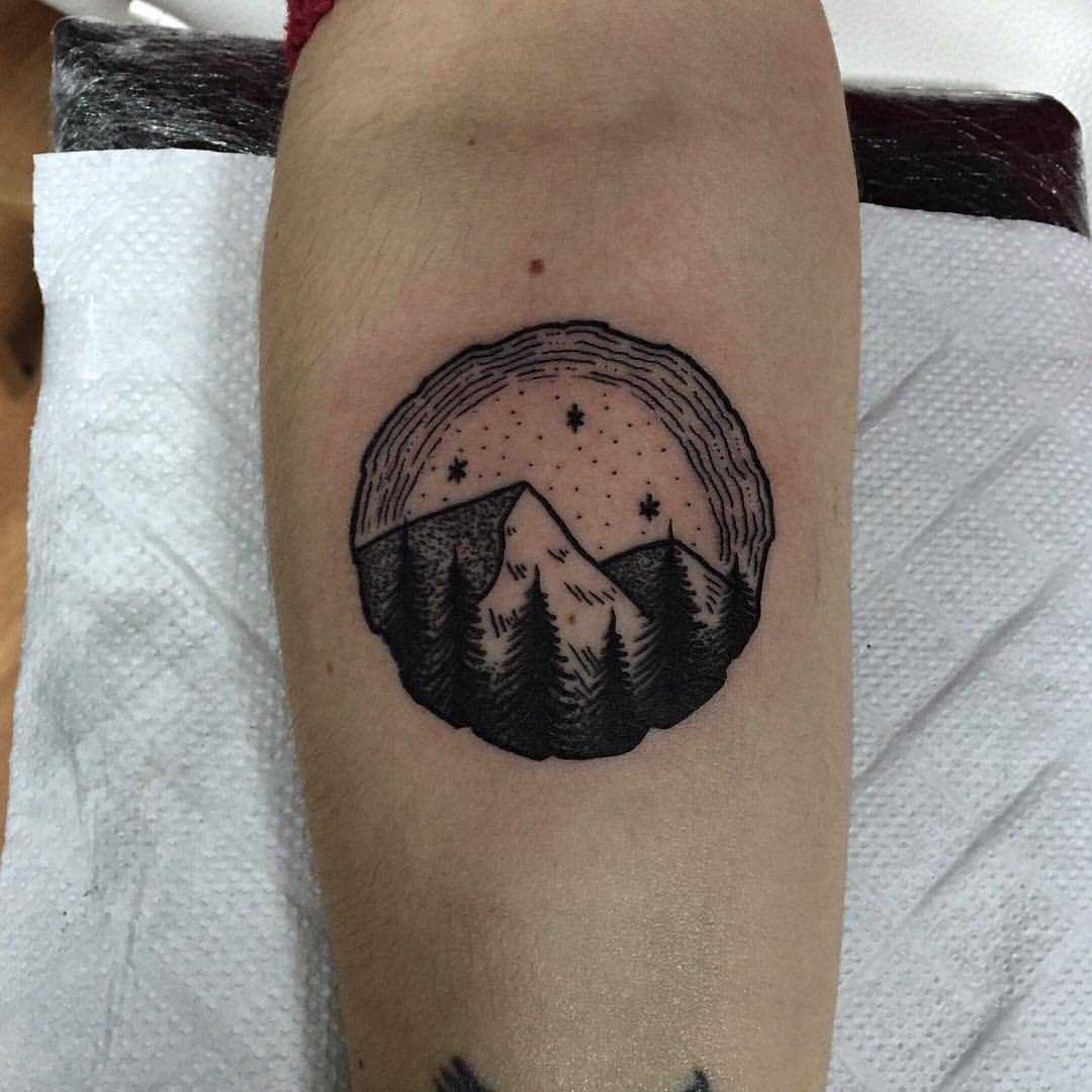 Wood slice-shaped landscape tattoo
