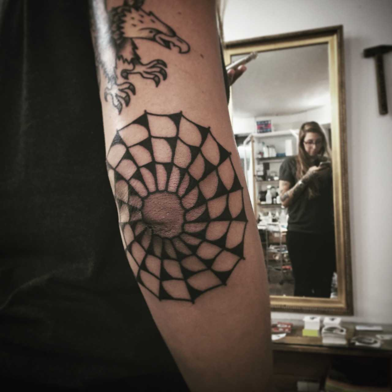 Black spider web elbow tattoo