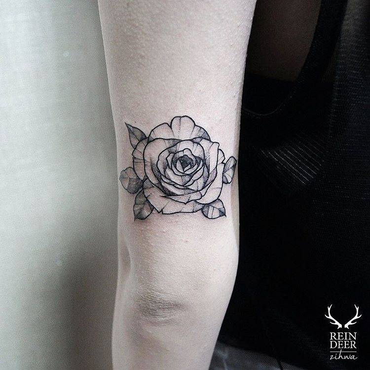 Blackwork style rose tattoo on the triceps