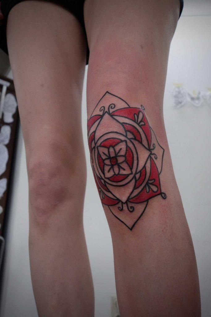 Red mandala tattoo on the knee