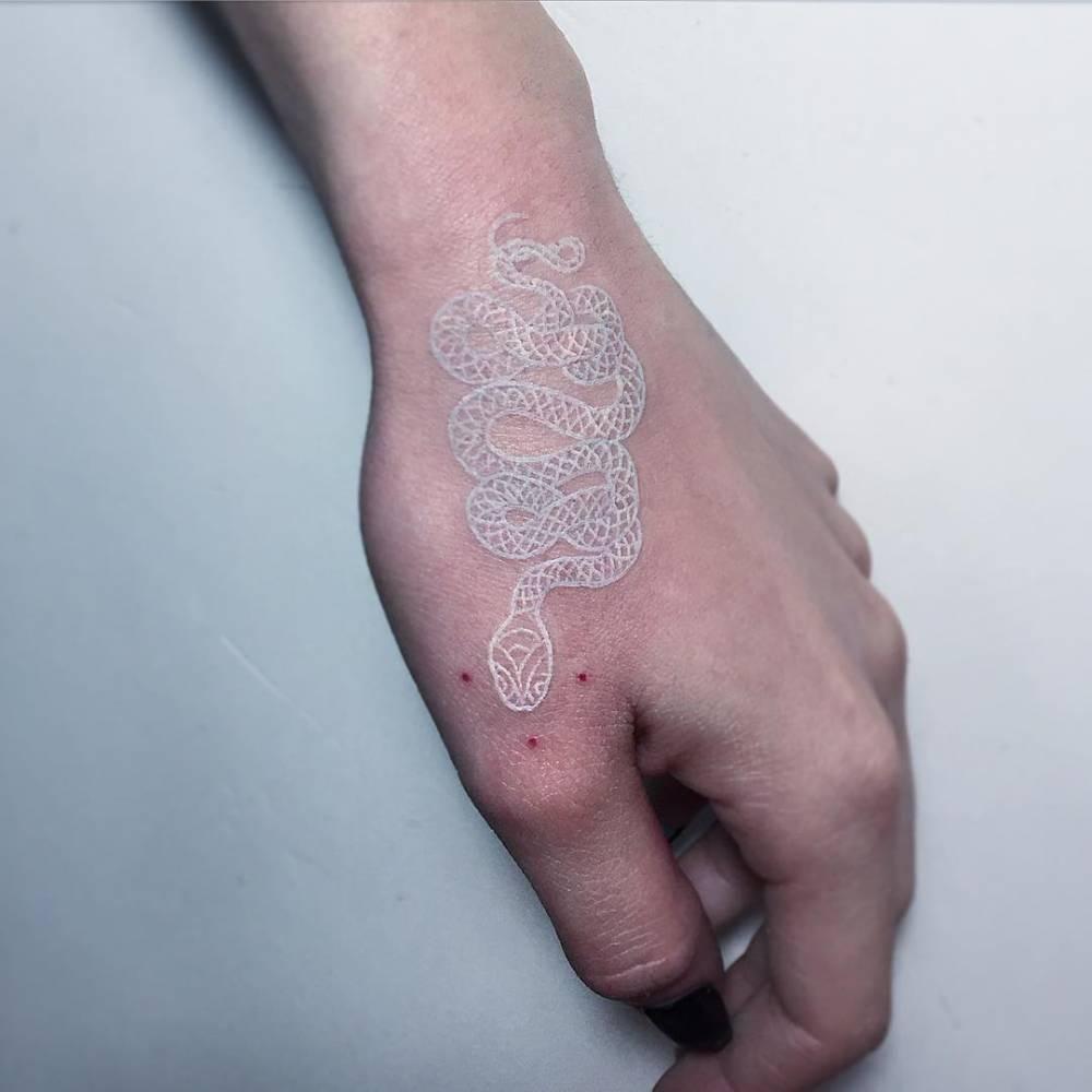 White snake tattoo on the left hand