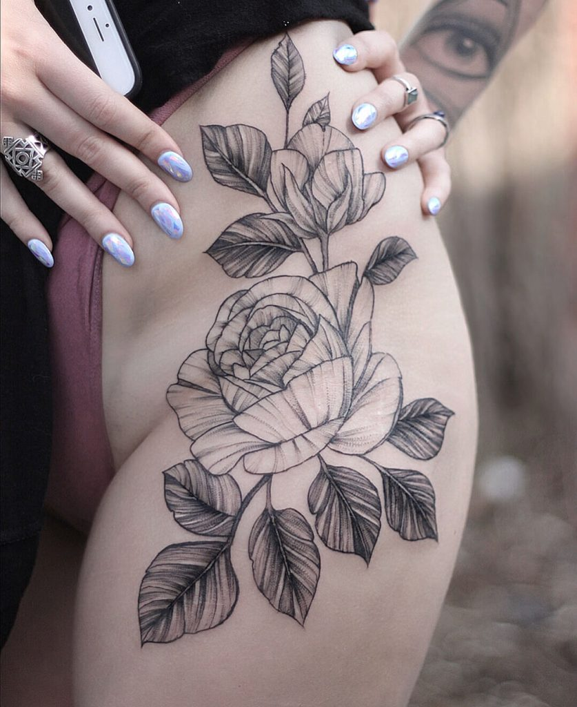 Black and grey rose tattoo on the hip