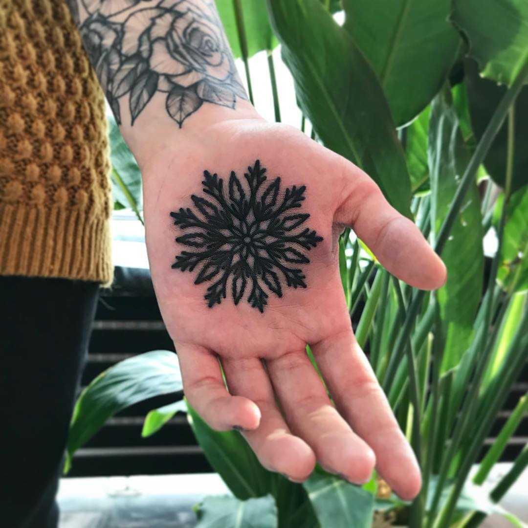 Black snowflake tattoo by Łukasz Krupiński