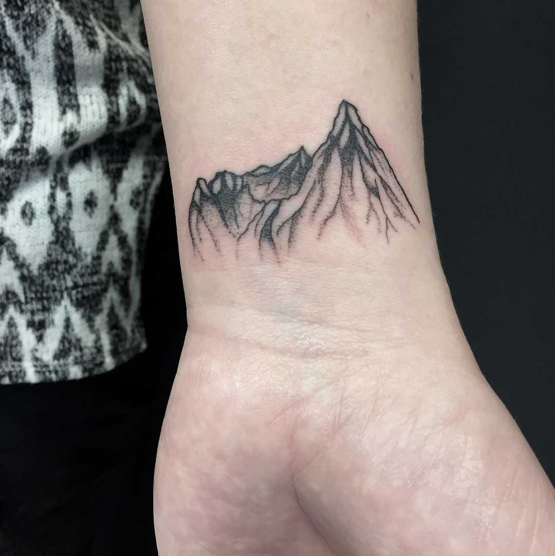 Blackwork mountain tattoo on the wrist