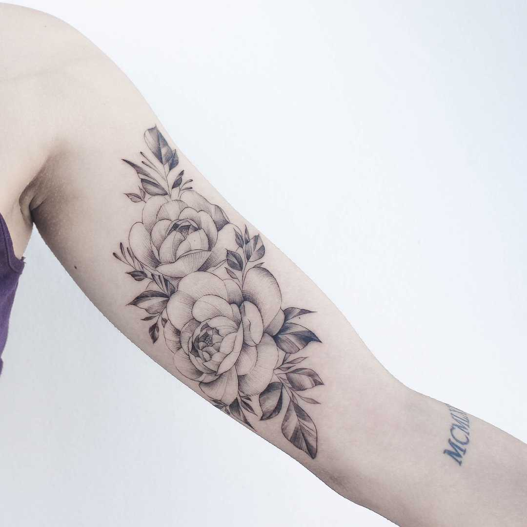 Grey rose tattoo on the arm