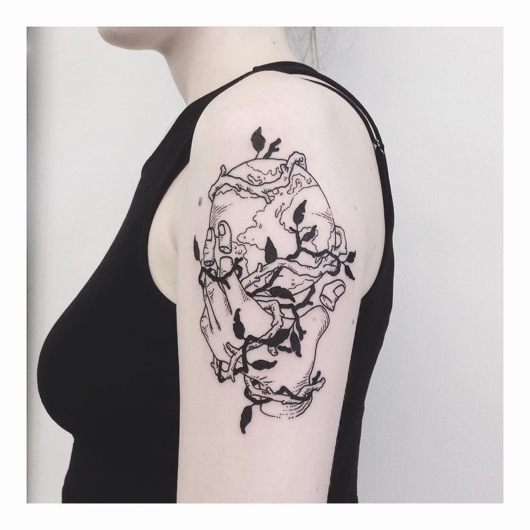 Hand holding Earth tattoo