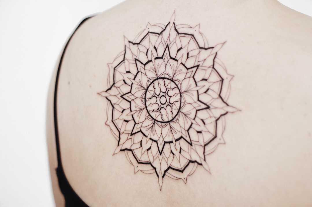 Large black and grey mandala tattoo on the back