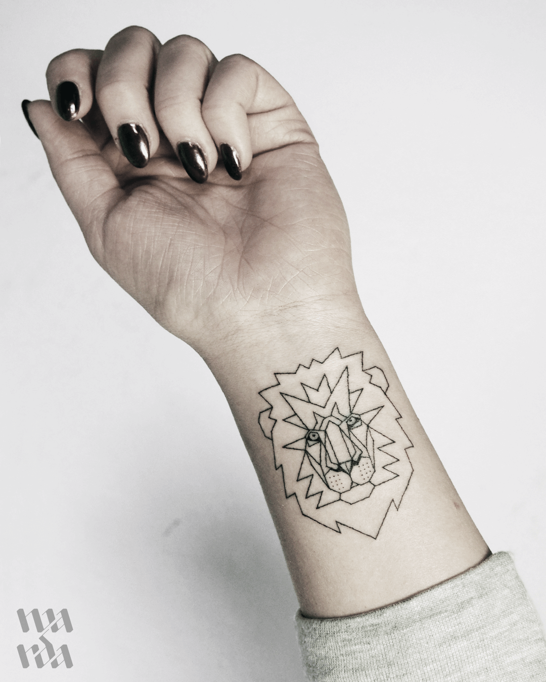 Lion tattoo on the wrist by Warda