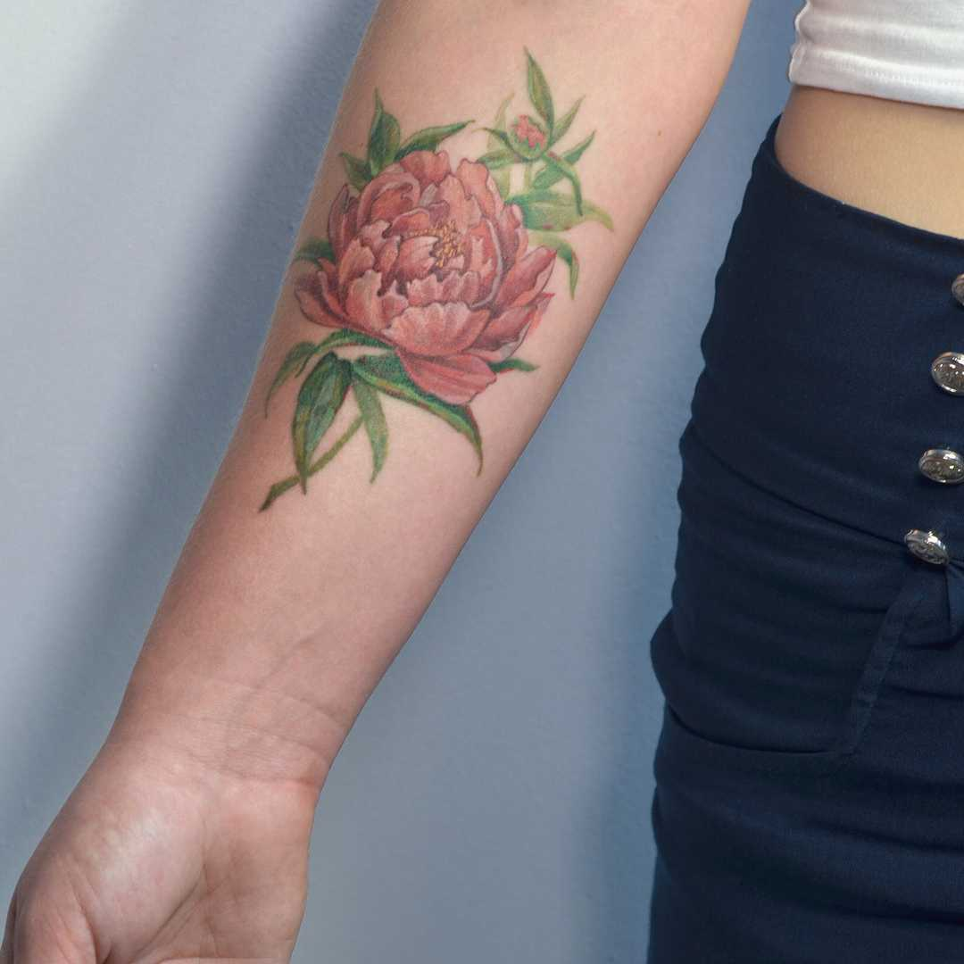 Realistic peony tattoo on the forearm
