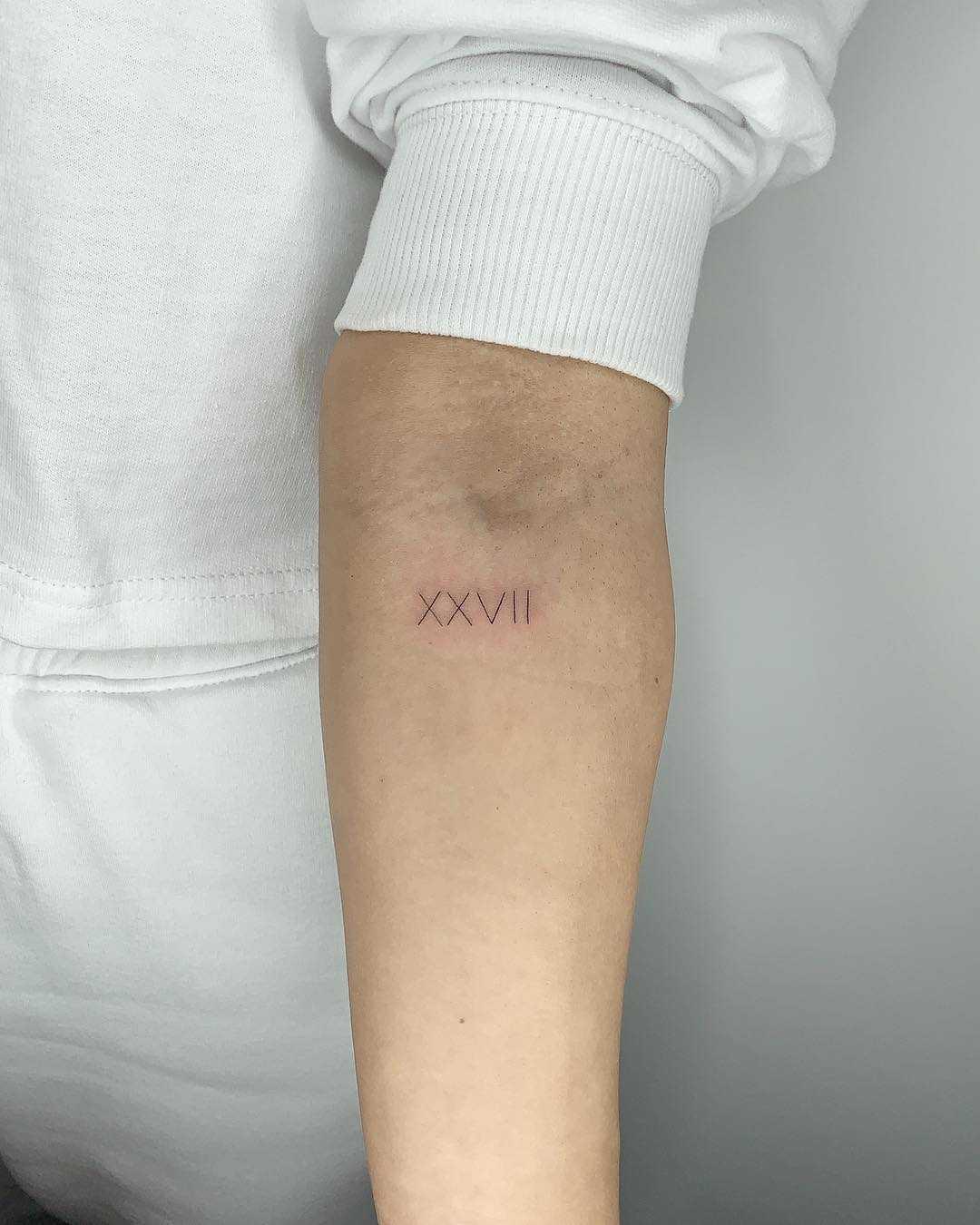 Roman numerals tattoo by Conz Thomas