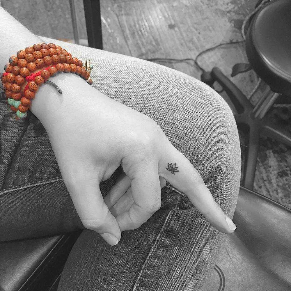 Tiny Lotus tattoo on a finger