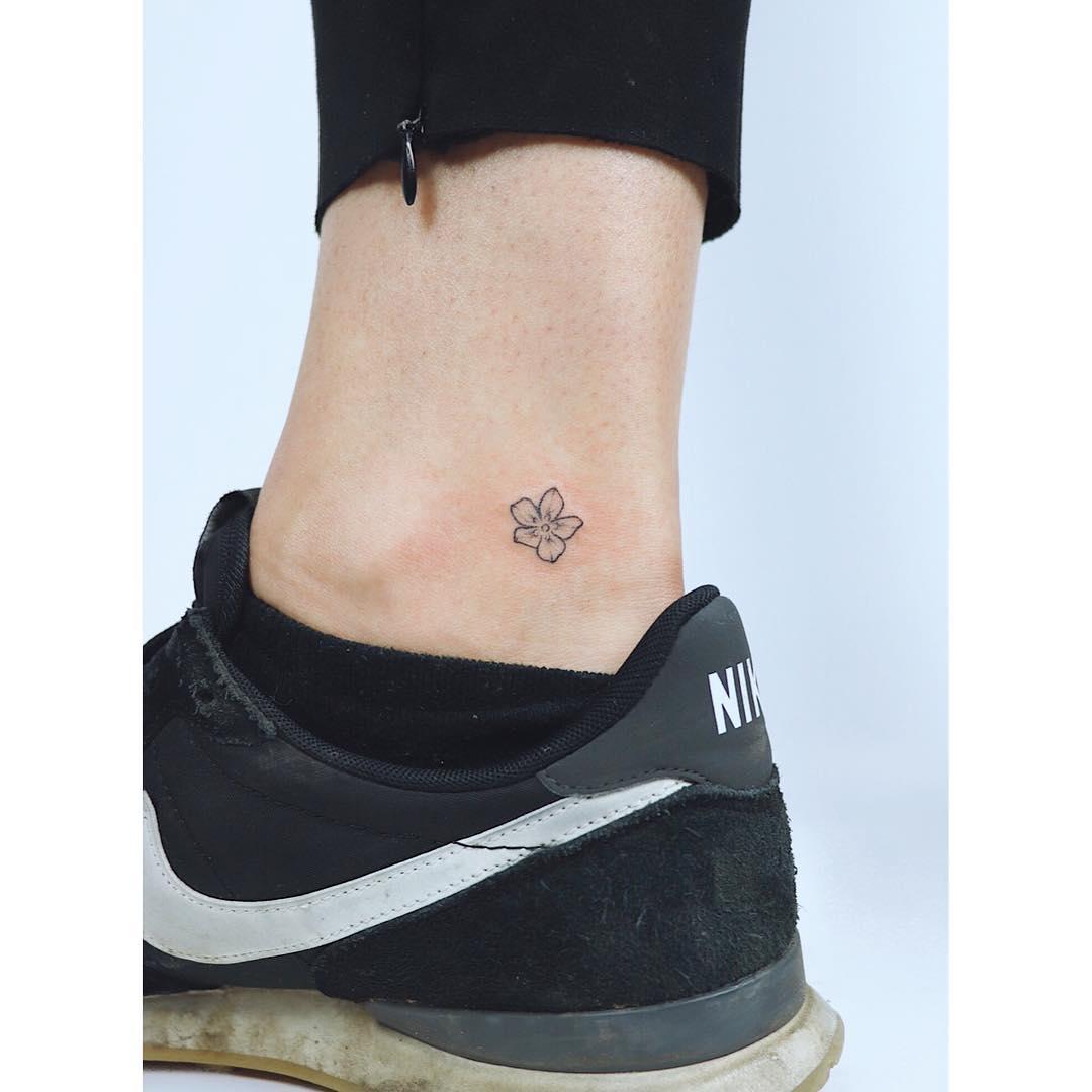 Tiny ankle flower by tattooist Zaya