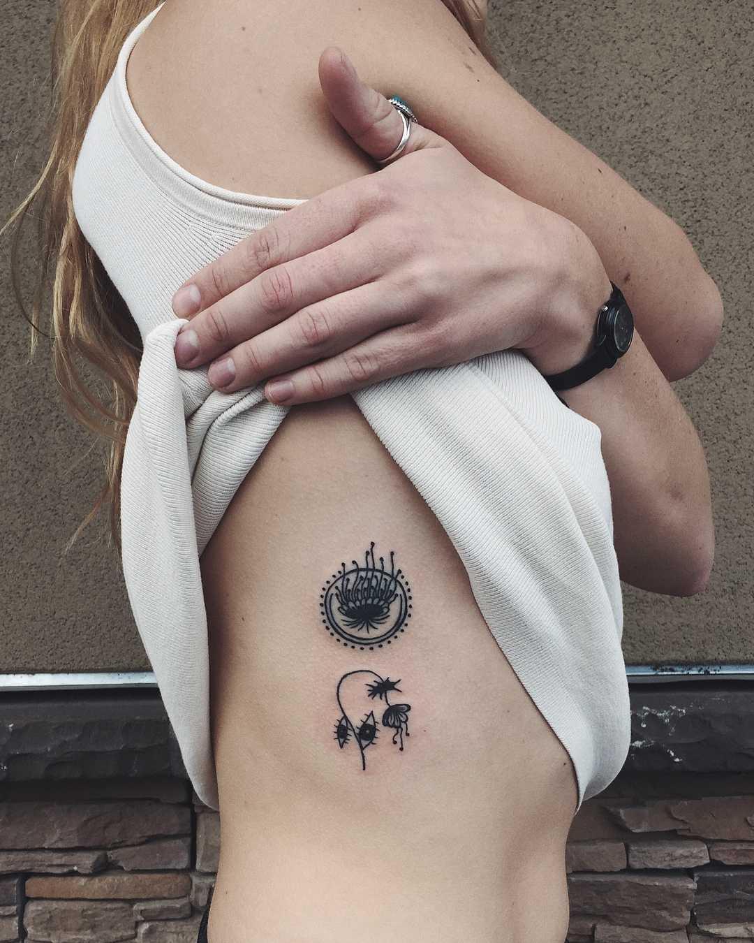 Tiny botanical tattoos on the rib