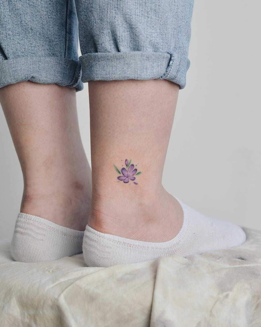 Violet flower tattoo on the ankle