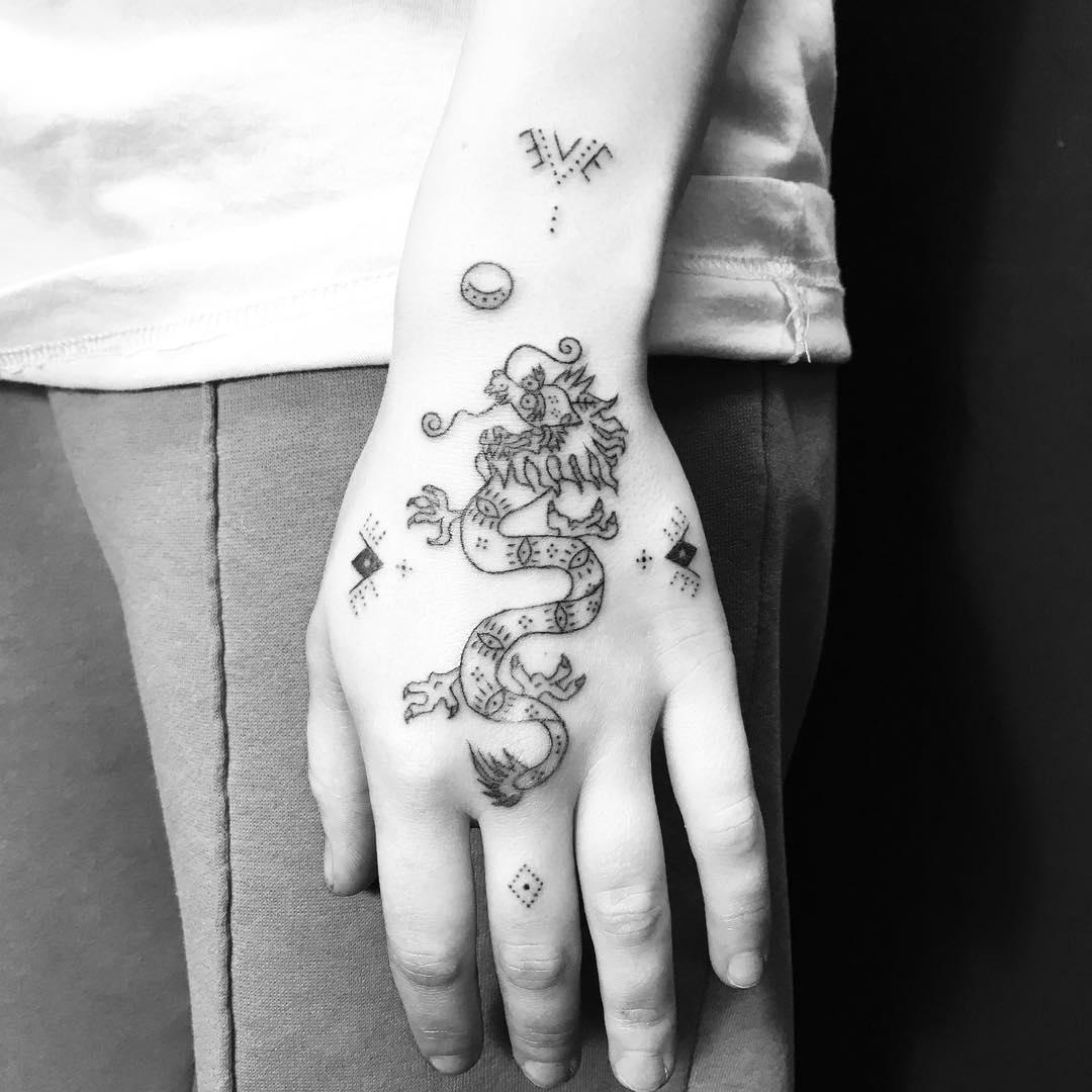 Hand-poked dragon tattoo by Nadia Rose