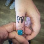 Little bow tattoo by Kirk Budden