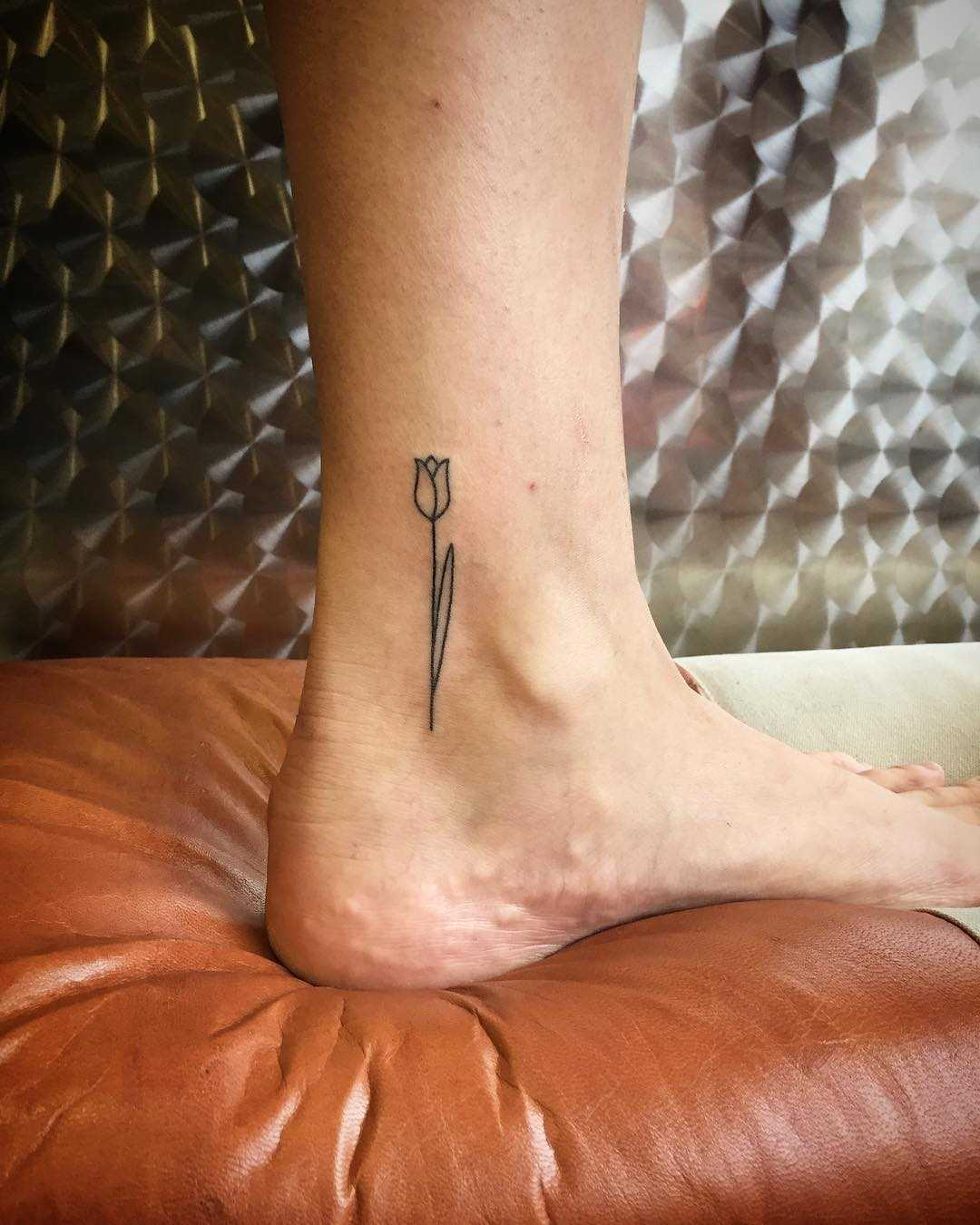 Little tulip tattoo on an ankle by Kirk Budden