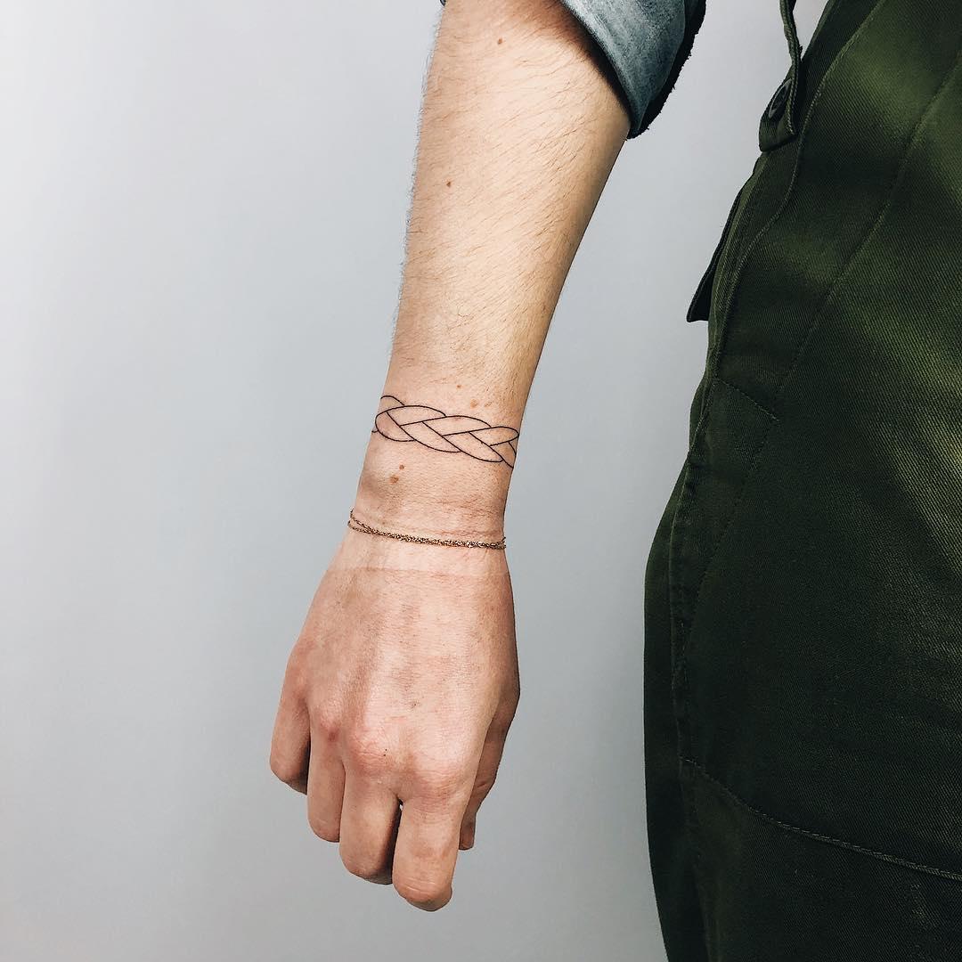 Minimalist woven bracelet tattoo by Kelli Kikcio
