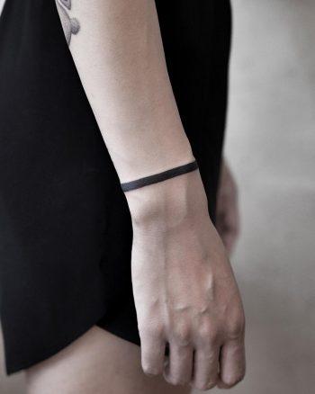 Solid black bracelet tattoo by Aki Wong