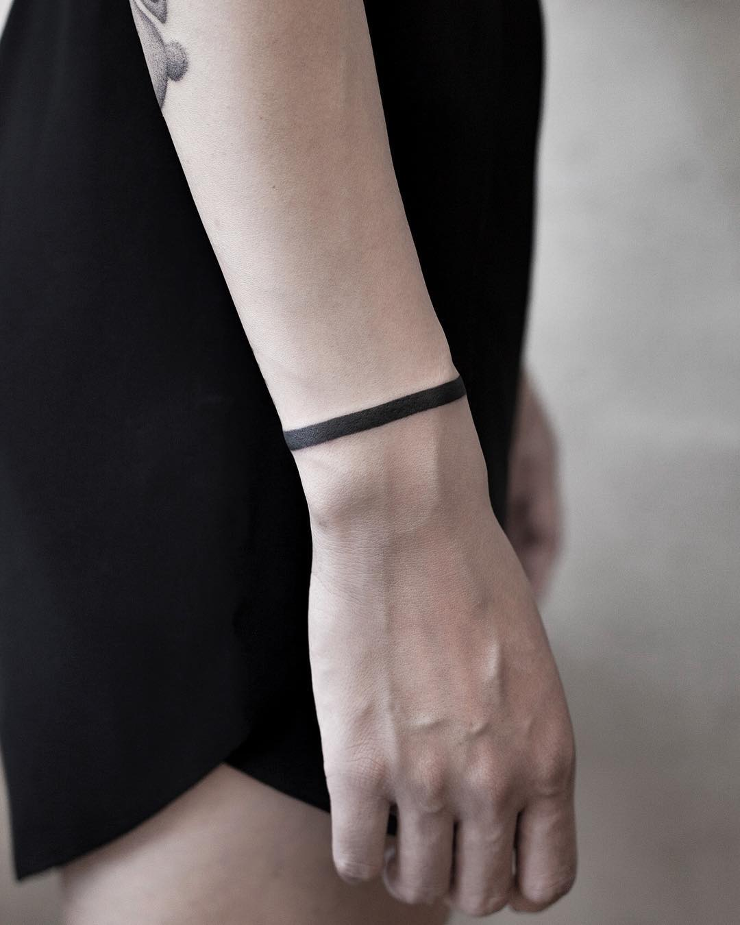 Solid black bracelet tattoo by Aki Wong