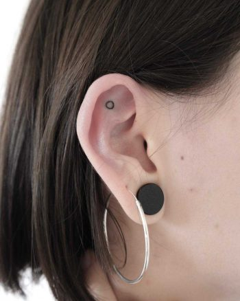 Tiny circle tattoo on the ear by Ann Gilberg