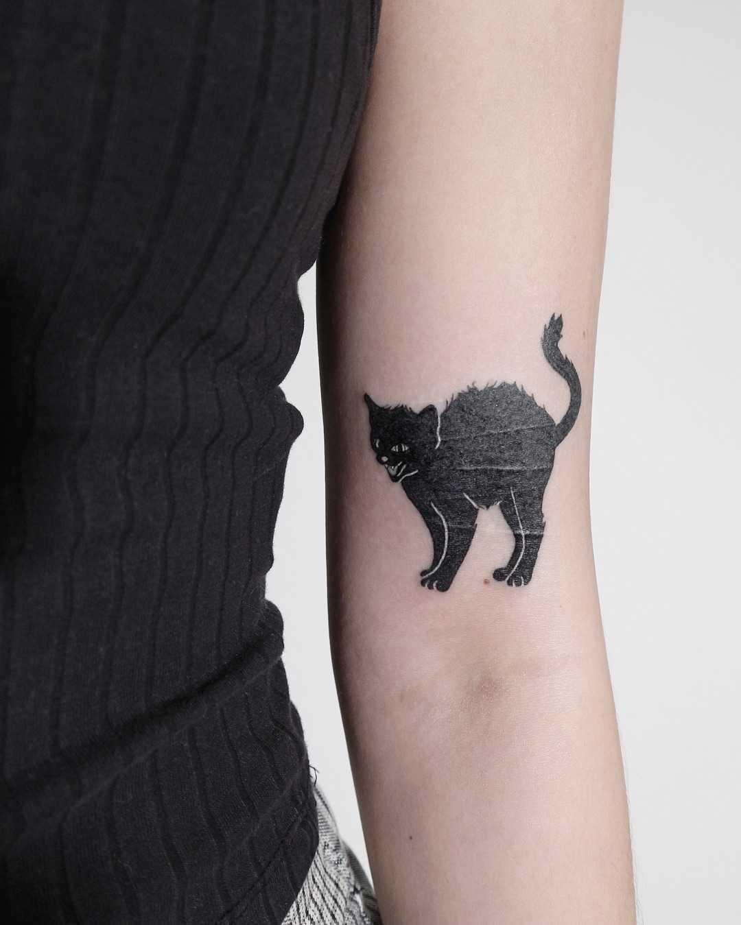 Black cat tattoo by Ann Gilberg