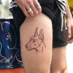 Dog on a thigh by Hand Job Tattoo