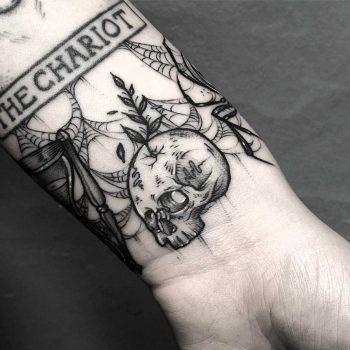Skull tattoo on a wrist by Lozzy Bones