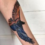 A flame colored raven tattoo by Mavka Leesova