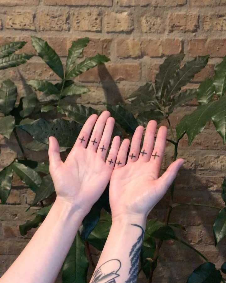 Plus sign + tattoos on fingers by Tine DeFiore
