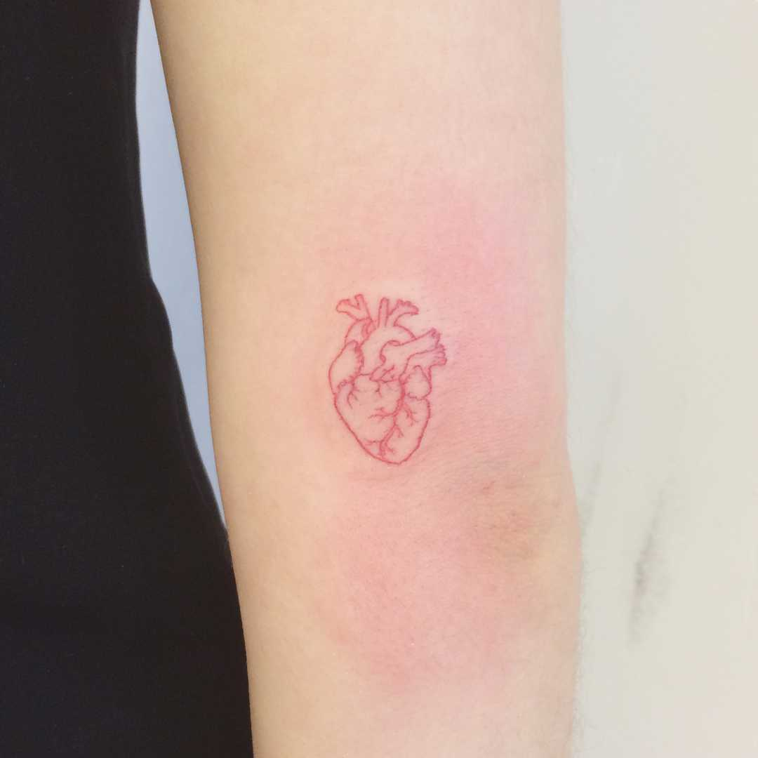 A tiny red heart tattoo by Annelie Fransson