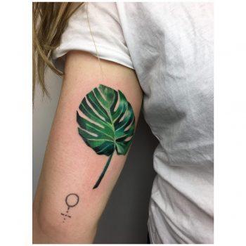 Colorful Monstera leaf tattoo by Mavka Leesova