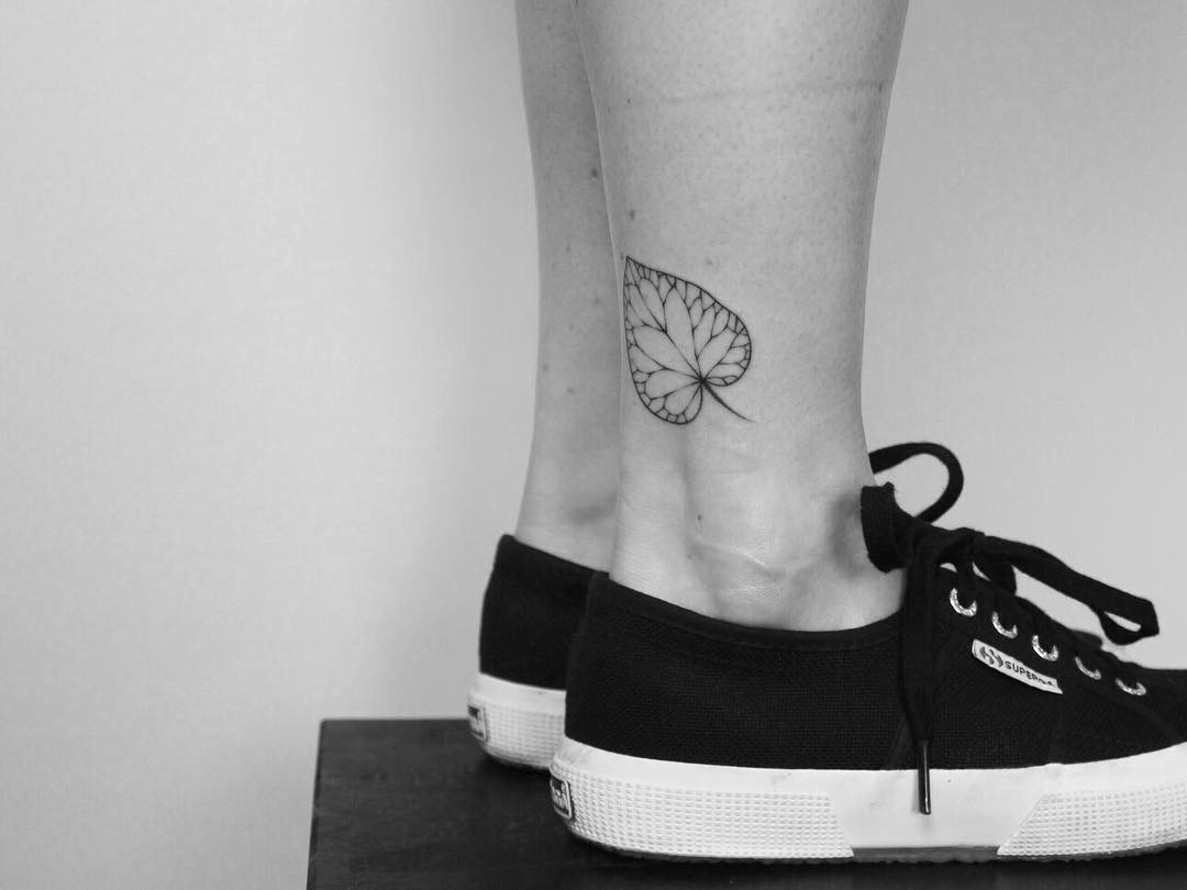 Hand-poked leave on an ankle by Lara Maju