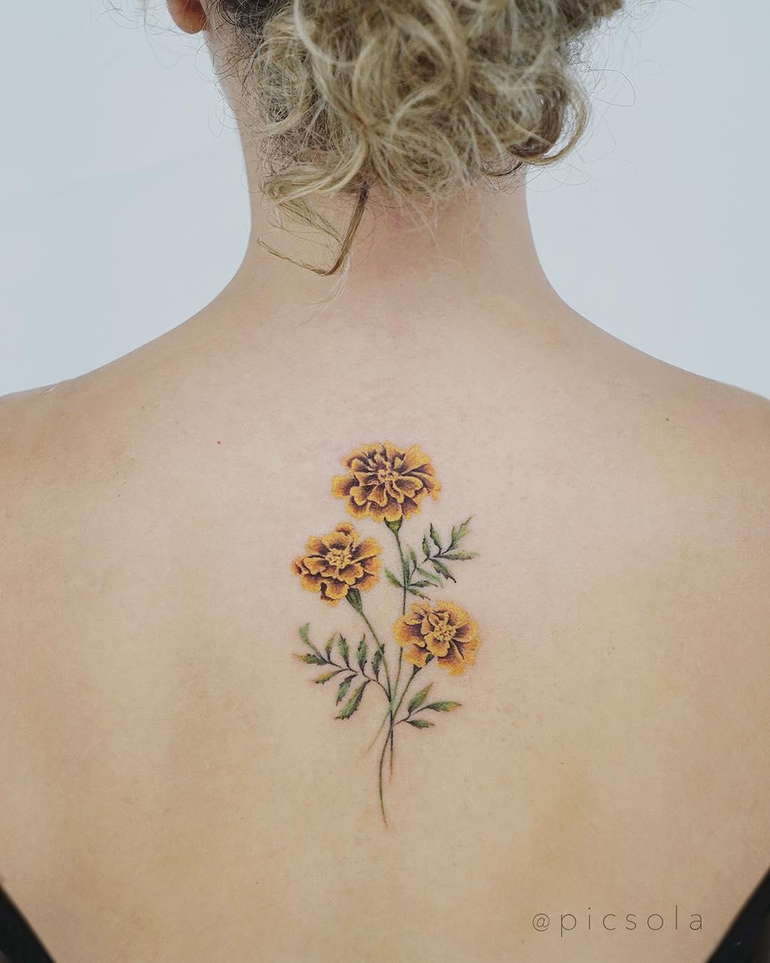 Marigold tattoo on the back by tattooist picsola