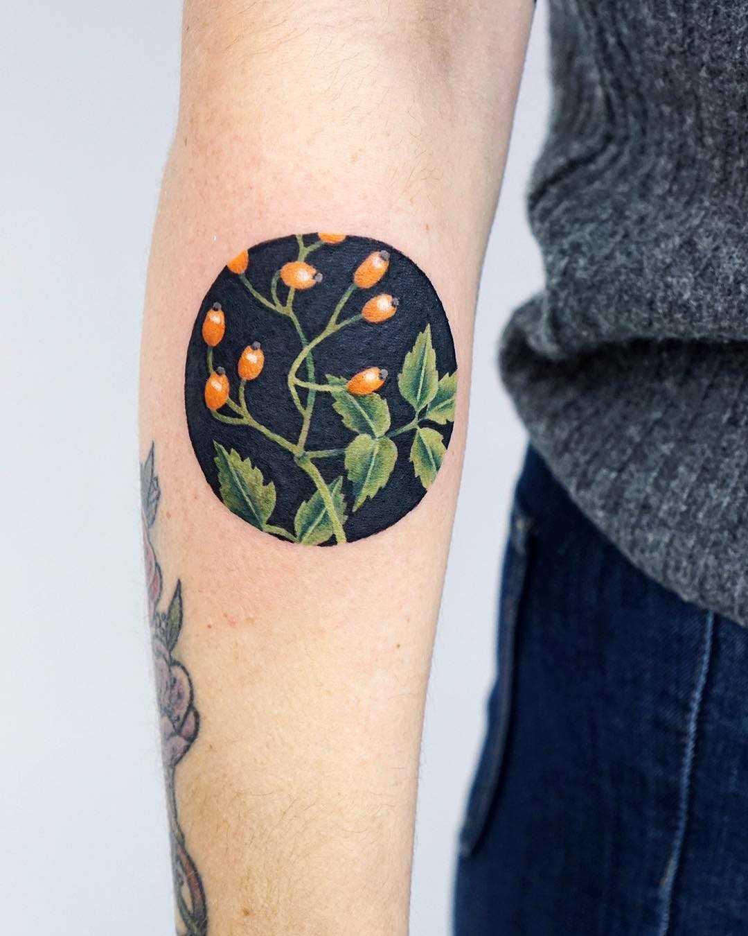Rose hip tattoo by tattooist picsola